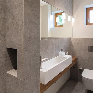 Cette photo montre un petit WC et toilettes tendance avec un WC suspendu, un carrelage gris, des carreaux de béton, un mur blanc, un sol en carreaux de ciment, une vasque, un plan de toilette en bois et un sol gris.