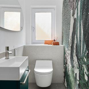 Пример оригинального дизайна: маленький туалет в современном стиле с плоскими фасадами, зелеными фасадами, инсталляцией, серой плиткой, белыми стенами и серым полом