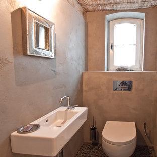 ハンブルクの小さいラスティックスタイルのおしゃれなトイレ・洗面所 (壁掛け式トイレ、グレーの壁、玉石タイル、壁付け型シンク) の写真