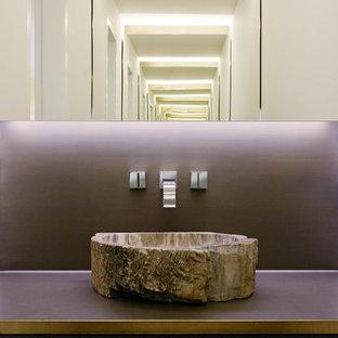 На фото: туалеты в стиле модернизм с настольной раковиной, плоскими фасадами, темными деревянными фасадами и коричневыми стенами