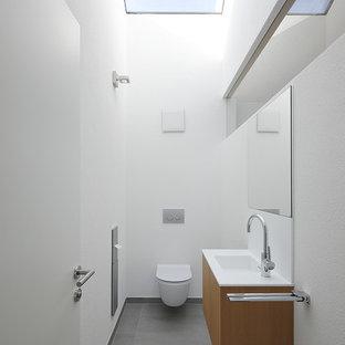 Mittelgroße Moderne Gästetoilette mit flächenbündigen Schrankfronten, hellbraunen Holzschränken, Wandtoilette mit Spülkasten, weißer Wandfarbe, integriertem Waschbecken und grauem Boden in München