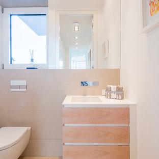 Aménagement d'un petit WC et toilettes contemporain avec un placard à porte plane, des portes de placard en bois clair, un WC suspendu, un carrelage beige, un carrelage de pierre, un mur blanc, un lavabo encastré, un plan de toilette en surface solide, un sol beige et un plan de toilette blanc.