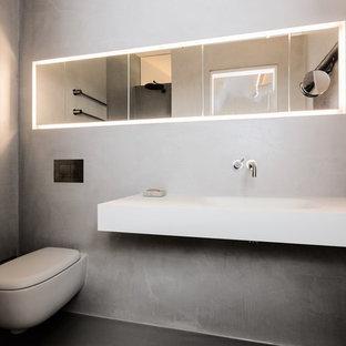 Kleine Moderne Gästetoilette mit flächenbündigen Schrankfronten, Wandtoilette, grauen Fliesen, grauer Wandfarbe, Betonboden, Trogwaschbecken, Mineralwerkstoff-Waschtisch und grauem Boden in München