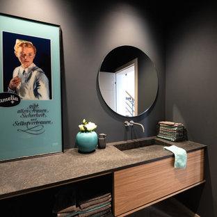 Mittelgroße Moderne Gästetoilette mit flächenbündigen Schrankfronten, schwarzer Wandfarbe, hellem Holzboden, integriertem Waschbecken, Granit-Waschbecken/Waschtisch, beigem Boden, schwarzer Waschtischplatte, eingebautem Waschtisch und hellbraunen Holzschränken in Sonstige