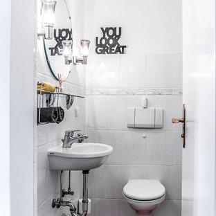 Esempio di un piccolo bagno di servizio con WC sospeso, piastrelle grigie, piastrelle in ceramica, pareti bianche, pavimento in terracotta e lavabo sospeso