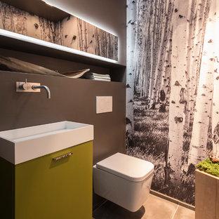 Diseño de aseo contemporáneo, pequeño, con armarios con paneles lisos, puertas de armario amarillas, sanitario de pared, paredes marrones, suelo de azulejos de cemento, lavabo sobreencimera y suelo negro
