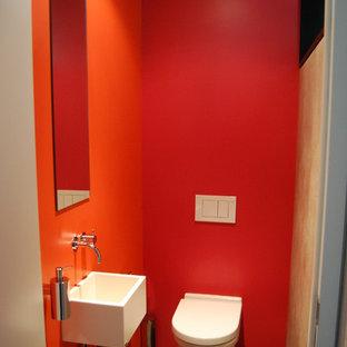 Foto di un piccolo bagno di servizio minimal con WC a due pezzi, pareti rosse, pavimento in terracotta, lavabo sospeso, top in superficie solida e pavimento grigio