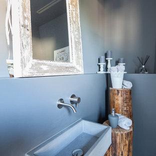 Imagen de aseo romántico, de tamaño medio, con paredes grises, lavabo suspendido, encimera de cemento, armarios abiertos, puertas de armario blancas, sanitario de pared, baldosas y/o azulejos azules, suelo de madera clara y suelo marrón