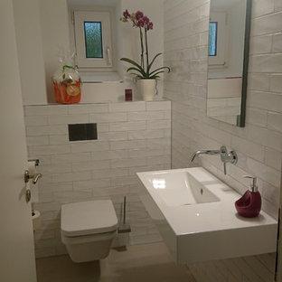 Новый формат декора квартиры: маленький туалет в современном стиле с раздельным унитазом, белой плиткой, плиткой кабанчик, белыми стенами, подвесной раковиной, бежевым полом, плоскими фасадами, синими фасадами, полом из керамической плитки, столешницей из нержавеющей стали и белой столешницей