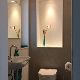На фото: маленький туалет в современном стиле с раздельным унитазом, серыми стенами, бетонным полом, подвесной раковиной и серым полом с