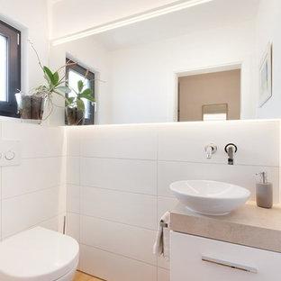 Пример оригинального дизайна: маленький туалет в современном стиле с плоскими фасадами, белыми фасадами, раздельным унитазом, белой плиткой, керамической плиткой, белыми стенами, светлым паркетным полом, настольной раковиной, столешницей из талькохлорита, коричневым полом и коричневой столешницей