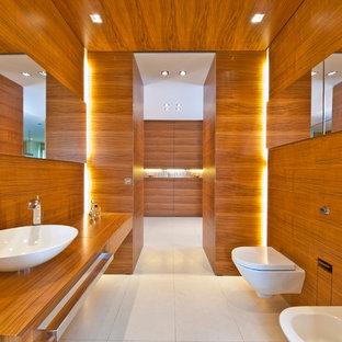 Réalisation d'un grand WC et toilettes design avec une vasque, des portes de placard en bois brun, un WC suspendu, un placard à porte plane, un plan de toilette en bois, un mur marron et un plan de toilette marron.