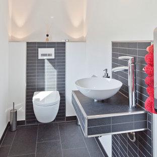 Moderne Gästetoilette mit weißer Wandfarbe, grauem Boden, Toilette mit Aufsatzspülkasten, grauen Fliesen, Aufsatzwaschbecken und grauer Waschtischplatte in Nürnberg