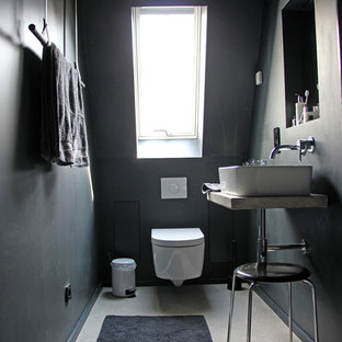 Photo of a small industrial powder room in Berlin with a vessel sink, a wall-mount toilet, black walls, concrete floors and concrete benchtops.