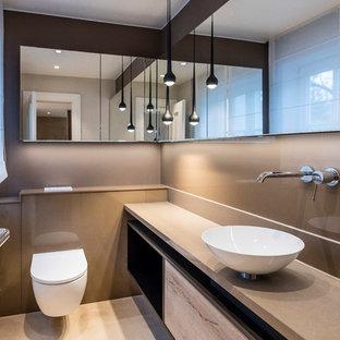 Bild på ett funkis beige beige toalett, med släta luckor, skåp i ljust trä, en vägghängd toalettstol, beige kakel, bruna väggar, ett fristående handfat och beiget golv