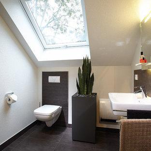Ispirazione per un bagno di servizio minimal con WC sospeso, piastrelle grigie, pareti beige, pavimento in terracotta, lavabo sospeso, pavimento grigio e top bianco