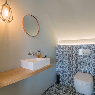 Kleine Retro Gästetoilette mit Wandtoilette, blauen Fliesen, Zementfliesen, weißer Wandfarbe, Zementfliesen, Aufsatzwaschbecken, Waschtisch aus Holz, buntem Boden, offenen Schränken und brauner Waschtischplatte in München