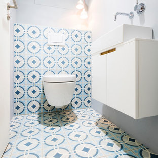 Inspiration for a small contemporary cloakroom in Munich with flat-panel cabinets, white cabinets, a two-piece toilet, blue tiles, white tiles, cement tiles, grey walls, cement flooring, a vessel sink and multi-coloured floors.