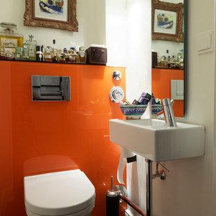 Idées déco pour un petit WC et toilettes contemporain avec un placard à porte plane, des portes de placard blanches, un WC séparé, des plaques de verre, un mur orange, un sol en bois foncé, un plan vasque, un plan de toilette en verre et un sol marron.