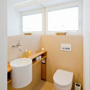 Ispirazione per un piccolo bagno di servizio design con nessun'anta, WC sospeso, pareti beige, top in legno, piastrelle beige, lavabo sospeso, piastrelle in pietra, pavimento beige e top marrone