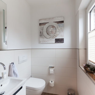Kleine Maritime Gästetoilette mit flächenbündigen Schrankfronten, weißen Schränken, Wandtoilette, beigefarbenen Fliesen, Keramikfliesen, weißer Wandfarbe, Vinylboden, integriertem Waschbecken und braunem Boden in Bremen