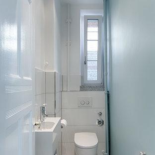 Ejemplo de aseo actual, pequeño, con baldosas y/o azulejos blancos, paredes azules, lavabo suspendido y suelo de terrazo