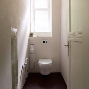 Exemple d'un WC et toilettes chic avec un WC suspendu, un carrelage vert et un sol violet.