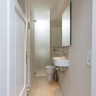 Exemple d'un petit WC et toilettes tendance avec un placard à porte plane, des portes de placard blanches, un WC suspendu, un carrelage beige, du carrelage en pierre calcaire, un mur beige, un sol en calcaire, un plan de toilette en calcaire, un sol beige et un lavabo suspendu.