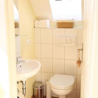Ispirazione per un bagno di servizio chic di medie dimensioni con WC sospeso, piastrelle bianche, piastrelle in ceramica, pareti gialle, pavimento in terracotta, lavabo sospeso e pavimento rosso