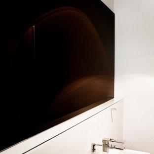 Foto di un grande bagno di servizio design con ante lisce, ante beige, WC sospeso, piastrelle beige, piastrelle di pietra calcarea, pareti bianche, pavimento in legno massello medio, lavabo a consolle, top in superficie solida e pavimento marrone
