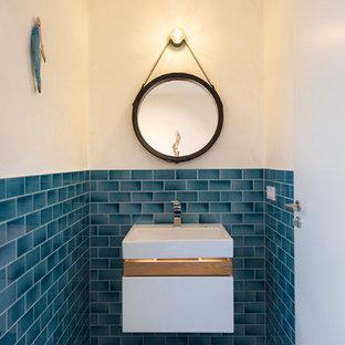 На фото: маленький туалет в скандинавском стиле с плоскими фасадами, белыми фасадами, синей плиткой, плиткой кабанчик, белыми стенами, настольной раковиной, столешницей из дерева и коричневой столешницей с