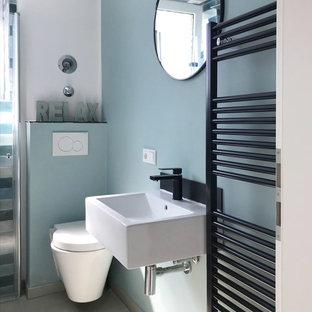 Ejemplo de aseo actual, pequeño, con paredes azules, suelo beige, sanitario de pared y lavabo suspendido