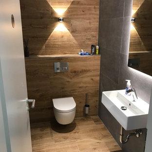 ハノーファーの小さいラスティックスタイルのおしゃれなトイレ・洗面所 (分離型トイレ、茶色いタイル、黒いタイル、壁付け型シンク、茶色い床) の写真