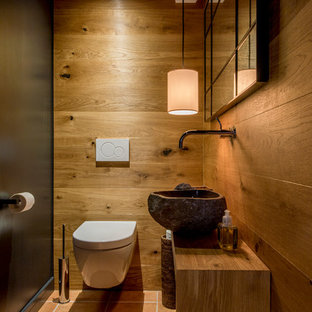 Cette photo montre un petit WC et toilettes montagne avec un WC suspendu, un mur noir, un sol en carreau de terre cuite, une vasque, un plan de toilette en bois, des portes de placard en bois brun, un sol rouge et un plan de toilette marron.