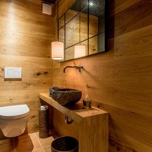 Inspiration för ett litet rustikt toalett, med en vägghängd toalettstol, ett fristående handfat, träbänkskiva, skåp i mellenmörkt trä, svarta väggar, klinkergolv i terrakotta och rött golv