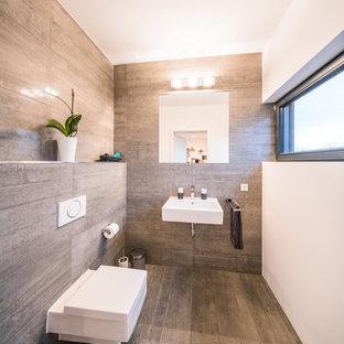 Kleine Moderne Gästetoilette mit Wandtoilette mit Spülkasten, beigefarbenen Fliesen, braunen Fliesen, weißer Wandfarbe, Wandwaschbecken und beigem Boden in Frankfurt am Main