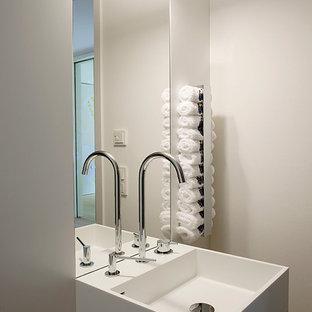 Idée de décoration pour un WC et toilettes design avec un placard à porte plane, des portes de placard blanches, un mur beige et un lavabo de ferme.