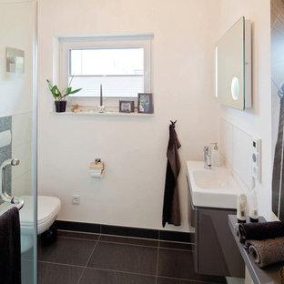 Esempio di un bagno di servizio contemporaneo con ante grigie, WC sospeso, piastrelle bianche, pareti bianche, lavabo a bacinella, pavimento nero e top bianco
