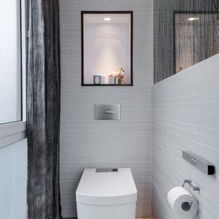 Kleine Moderne Gästetoilette mit Wandtoilette, grauem Boden und grauen Fliesen in Düsseldorf