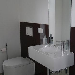 Cette photo montre un petit WC et toilettes tendance avec un WC séparé, un carrelage noir, des plaques de verre, un mur blanc, un lavabo suspendu et un sol gris.