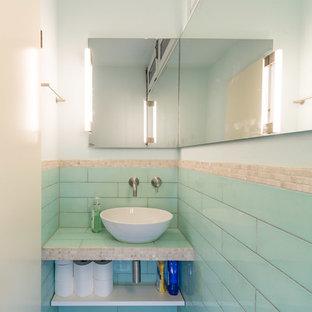 Esempio di un piccolo bagno di servizio minimal con WC sospeso, piastrelle blu, piastrelle in ceramica, pareti blu, pavimento in pietra calcarea, lavabo a bacinella, top piastrellato e pavimento beige