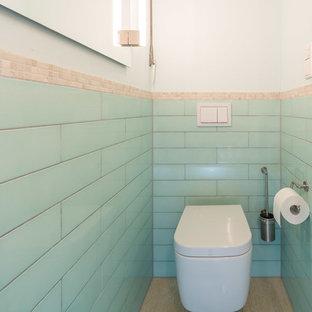 Idee per un piccolo bagno di servizio minimal con WC sospeso, piastrelle blu, piastrelle in ceramica, pareti blu, pavimento in pietra calcarea, lavabo a bacinella, top piastrellato e pavimento beige