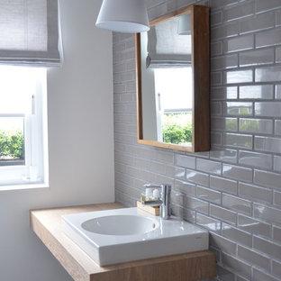 Elegant Moderne Gästetoilette Mit Grauen Fliesen, Aufsatzwaschbecken, Waschtisch  Aus Holz, Metrofliesen, Grauer Wandfarbe