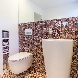 シュトゥットガルトの小さいコンテンポラリースタイルのおしゃれなトイレ・洗面所 (オープンシェルフ、白いキャビネット、壁掛け式トイレ、ベージュのタイル、茶色いタイル、オレンジのタイル、赤いタイル、黒いタイル、モザイクタイル、白い壁、モザイクタイル、ペデスタルシンク、マルチカラーの床) の写真