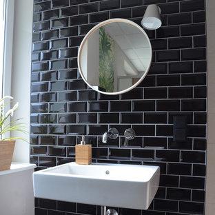 Foto de aseo urbano, pequeño, con baldosas y/o azulejos de cemento, paredes negras, suelo de baldosas de cerámica, lavabo suspendido y suelo gris