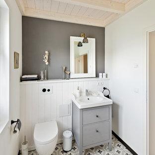Kleine Landhaus Gästetoilette mit flächenbündigen Schrankfronten, grauen Schränken, Wandtoilette, Porzellan-Bodenfliesen, Aufsatzwaschbecken, Waschtisch aus Holz, grauem Boden und grauer Wandfarbe in Nürnberg