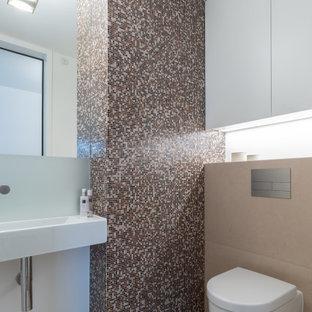 Moderne Gästetoilette mit Glasfliesen, Wandwaschbecken, Wandtoilette, farbigen Fliesen, weißer Wandfarbe und beigem Boden in Köln