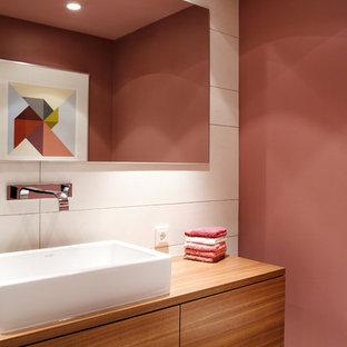 Idées déco pour un WC et toilettes contemporain de taille moyenne avec une vasque, un placard à porte plane, des portes de placard en bois brun, un mur rose, un carrelage blanc, un plan de toilette en bois et un plan de toilette marron.