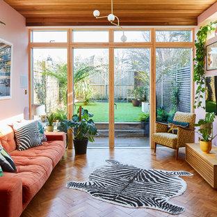 Modelo de sala de estar vintage con paredes rosas, suelo de madera en tonos medios, marco de chimenea de ladrillo y televisor colgado en la pared