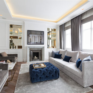 Design ideas for a classic family and games room in London with white walls, medium hardwood flooring, a standard fireplace and a wall mounted tv.